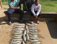 Roy Edmond and his Daughter, Simone and his son Trey with their limit of hybrid and stripers.IMG_2221